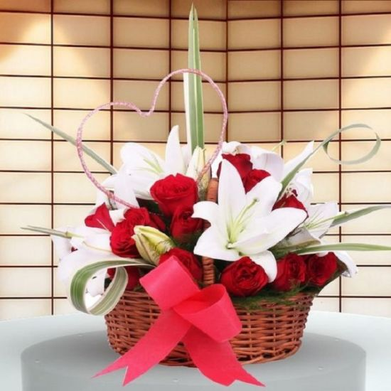 White lilies and red roses in a flower basket from JuneFlowers.com